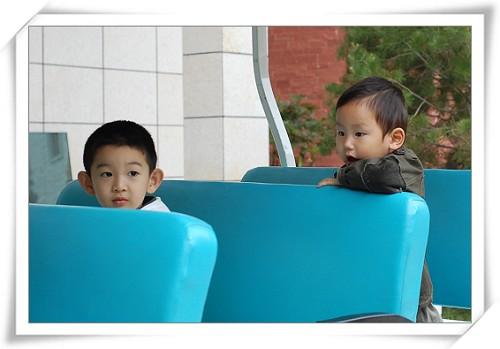 坐上电瓶车准备游山庄的小哥俩